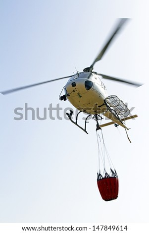 Firefighter helicopter with water bag - stock photo