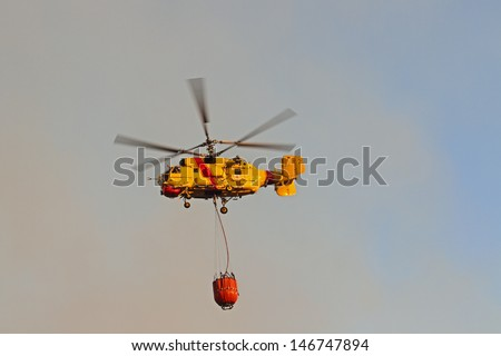 Firefighter helicopter with water bag in smokey air - stock photo