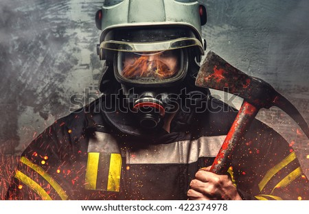 Firefighter in a sparks holds iron axe.