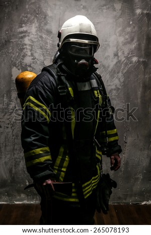 Firefighter in oxygen mask and axe on grey background.