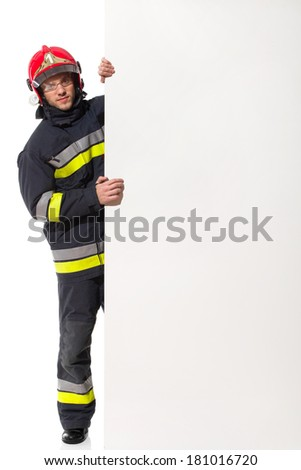 Firefighter in red helmet standing behind big placard and holding it. Full length studio shot isolated on white. - stock photo