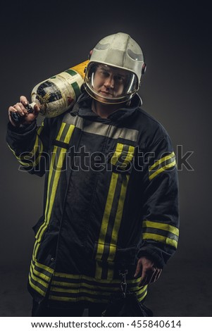 Firefighter in safety costume holding oxygen tank on his shoulder.