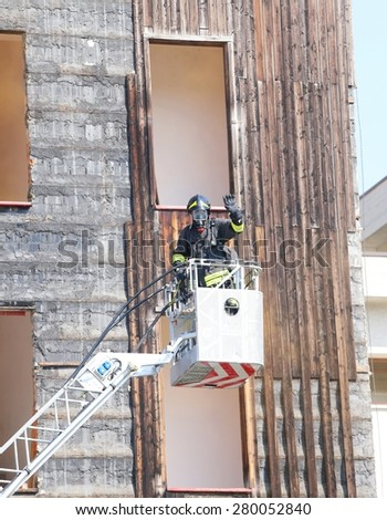 firefighter in the basket of the pumper fire engines during rescue operations - stock photo