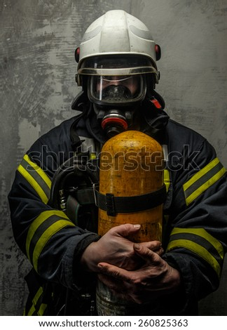 Firefighter in uniform with axe and oxygen on grey background
