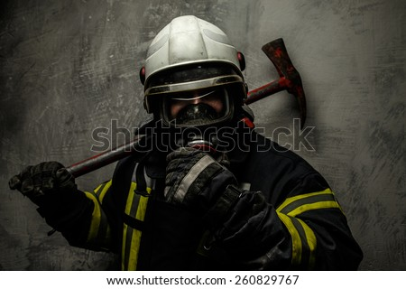 Firefighter in uniform with axe on grey background