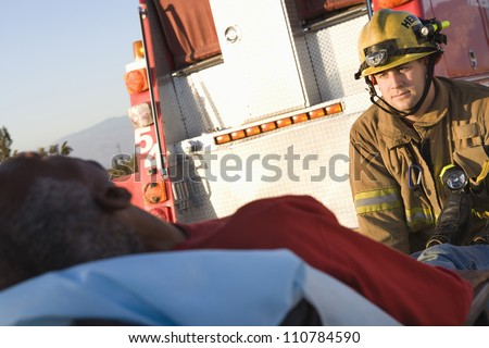 Firefighter looking at patient with ambulance in the background - stock photo