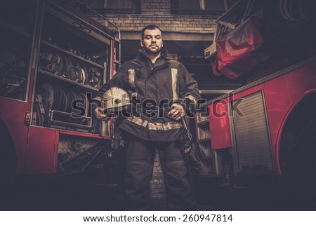 Firefighter near truck with equipment  - stock photo
