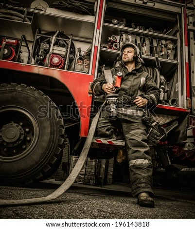 Firefighter near truck with equipment with water water hose over shoulder  - stock photo