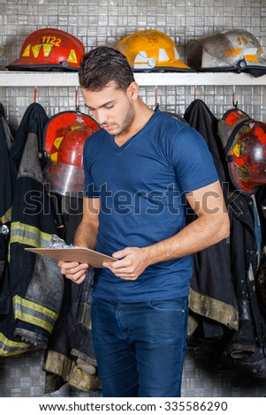 Firefighter reading clipboard against uniforms hanging at fire station - stock photo
