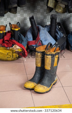 Firefighter's shoes on tiled floor at fire station - stock photo