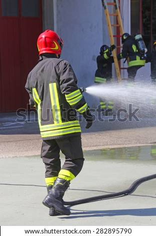 Firefighter sprays water with the spear fighting during the exercise in the fire station