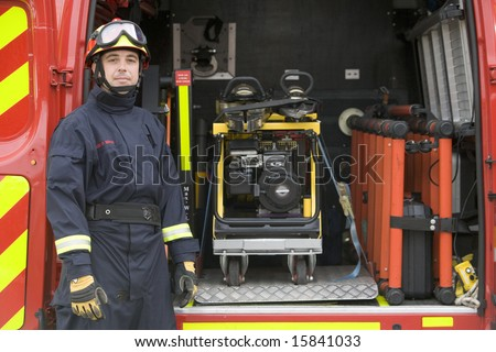 Firefighter standing by the equipment in a small fire engine