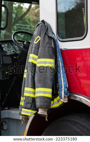 Firefighter suit Hanging on the Door of Fire Truck Closeup - stock photo