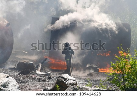 Firefighter trying to put water on a big fire - stock photo