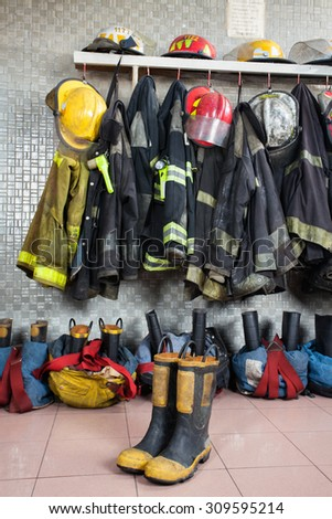Firefighter uniforms and gear arranged at fire station - stock photo