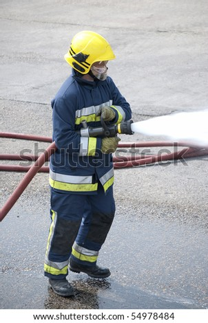 Firefighter using hose - stock photo