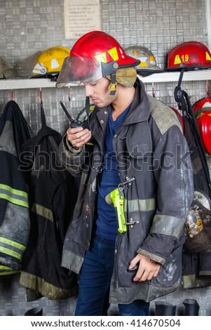 Firefighter Using Walkie Talkie In Fire Station - stock photo