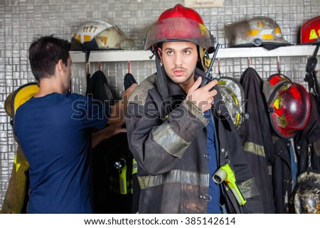 Firefighter Using Walkie Talkie With Colleague In Background - stock photo