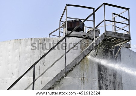 Firefighter water jet extinguish the fire started near a petrol storage tank - stock photo