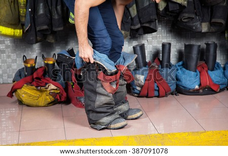 Firefighter Wearing Uniform At Fire Station - stock photo