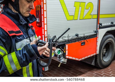 Firefighter with a walkie talkie next to an emergency vehicle - HDR