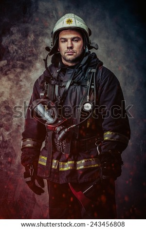 Firefighter with helmet and axe in a smoke - stock photo