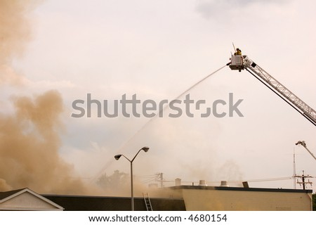firefighters and the smoke from burning building - stock photo