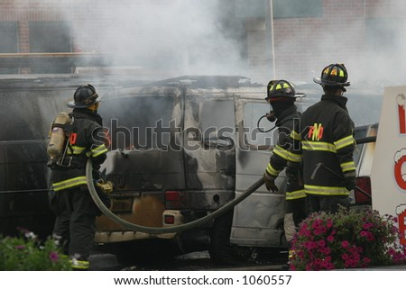 Firefighters at a vehicle fire. Editorial use only.