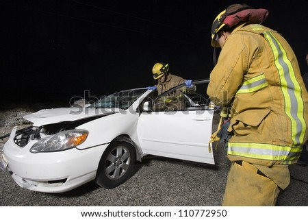 Firefighters at the site of car accident - stock photo