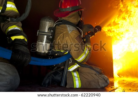 Firefighters attack a fire in a training prop.