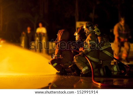 Firefighters attack a propane fire during a training exercise. - stock photo