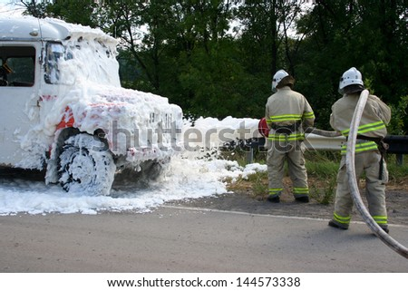 Firefighters extinguish a fire in a burning bus standing at the side of the road - stock photo