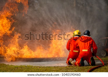 Firefighters fighting a fire operation, Water spray by high pressure nozzle to fire surround with smoke, Firefighters extinguish a house