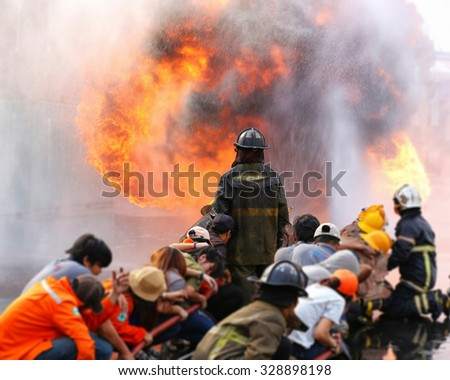 Firefighters fighting fire during training with worker - stock photo