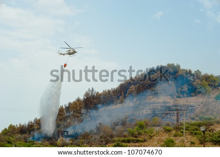 Firefighters helicopter in action, dumping water on a forest fire