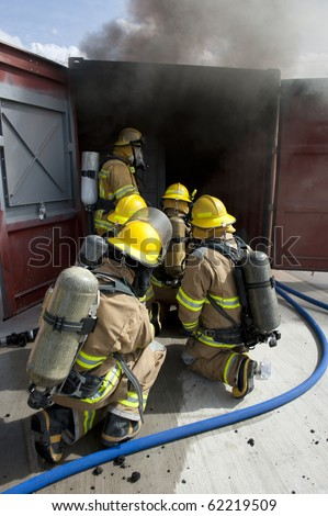 Firefighters line up during a training exercise. - stock photo