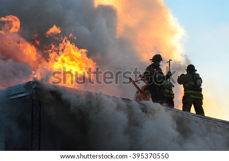 Firefighters on the roof of a house that is on fire - stock photo