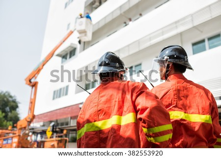 Firefighters or firemen are people whose job is to put out fires and rescue people. In a city, the building they work in is called a fire station, or fire hall - stock photo