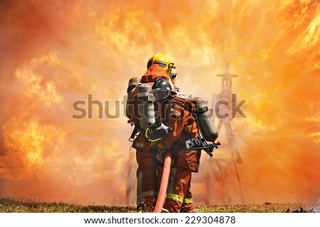 Firefighters prepare to attack a propane fire. - stock photo