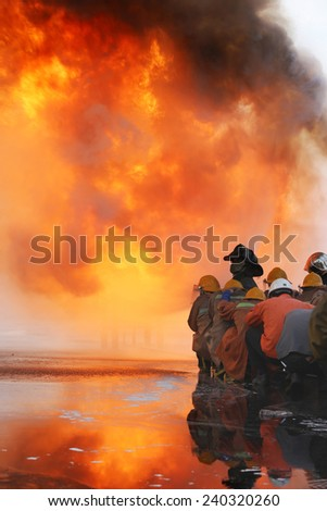 Firefighters prepare to attack a propane fire during training - stock photo