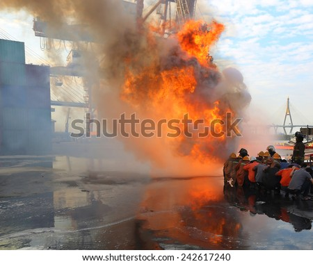Firefighters prepare to attack a propane fire during training at ship yard - stock photo