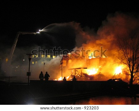 Firefighters putting out a burning house with crane - stock photo