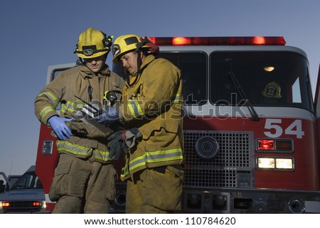Firefighters reading document with fire truck in the background - stock photo