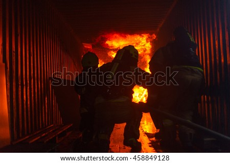 Firefighters standing in front of a blazing fire.