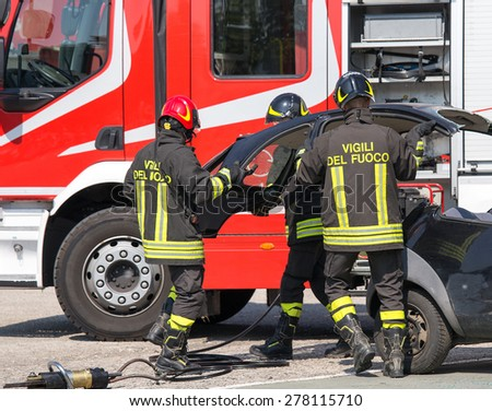 Firefighters take off the hood of the car after a serious road accident - stock photo