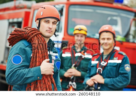 firefighters team in uniform in front of fire engine machine and fireman team - stock photo