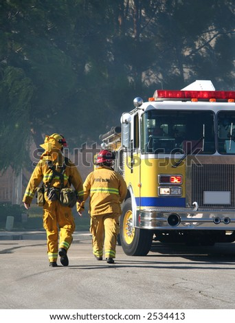 Firefighters walking toward a firetruck - stock photo