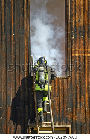 firefighters with oxygen cylinder to peg up the ladder to extinguish a dangerous fire with white smoke - stock photo