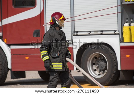 firefighters with the hose to put out the fires and the great firetruck - stock photo