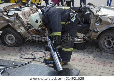 firefighters with the pneumatic shears open the car doors after a car accident